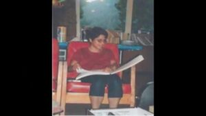 A girl sitting in a chair, reading a Braille book