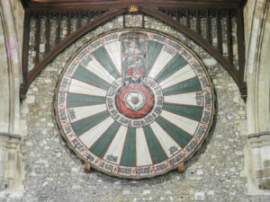 A medieval replica of King Arthur's legendary round table, hanging in Winchester Castle. The table features the Tudor Rose at its centre, with the outer design portraying Henry VIII as King Arthur on his throne, surrounded by 24 places, each bearing the name of one of the legendary Knights of the Round Table of King Arthur's court.