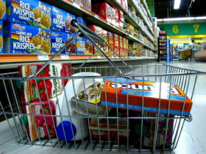 Groceries in a metal shopping basket. Shelves in a grocery store are visible in the background.